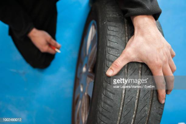 cropped image of mechanic repairing tire - somente adultos - fotografias e filmes do acervo