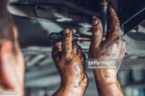 cropped image of mechanic repairing vehicle - dirty stock pictures, royalty-free photos & images