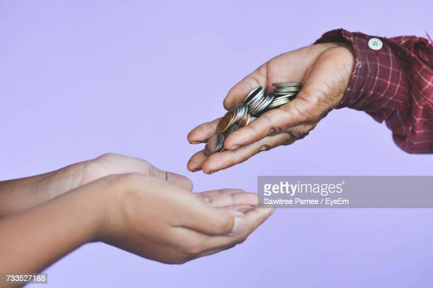 Cropped Image Of Men Giving Coins To Women Against Purple Background