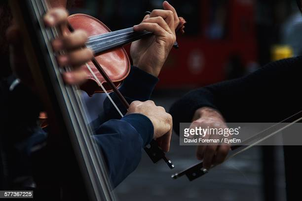 cropped image of men playing violins on street - musician stock photos and pictures