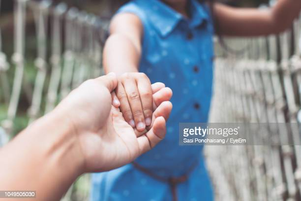 cropped image of mother and daughter holding hands - very young thai girls stock photos and pictures