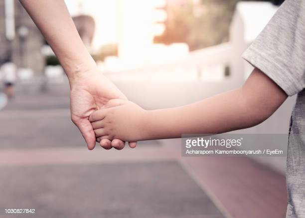 cropped image of mother and son holding hands on road - childhood stock pictures, royalty-free photos & images