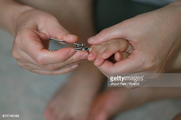 Cropped Image Of Mother Cutting Baby Boy Fingernail