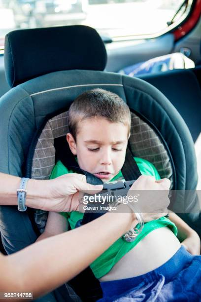 cropped image of mother fastening seat belt of sons car seat - fastening stock pictures, royalty-free photos & images