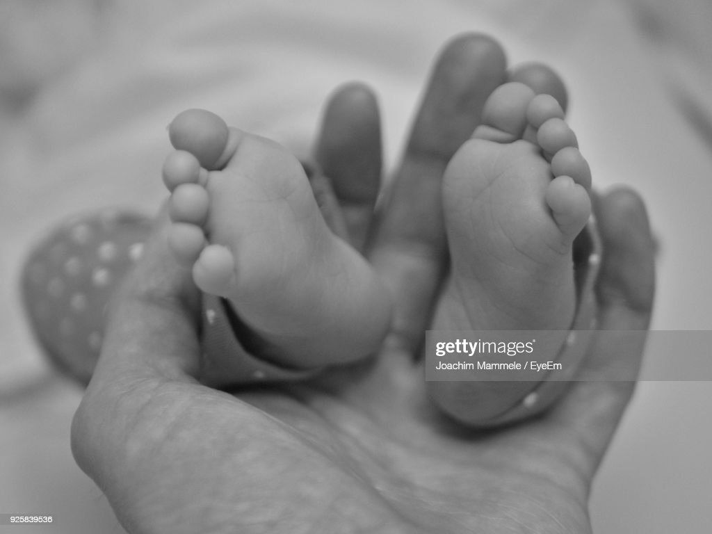 Cropped Image Of Mother Holding Baby Feet High Res Stock