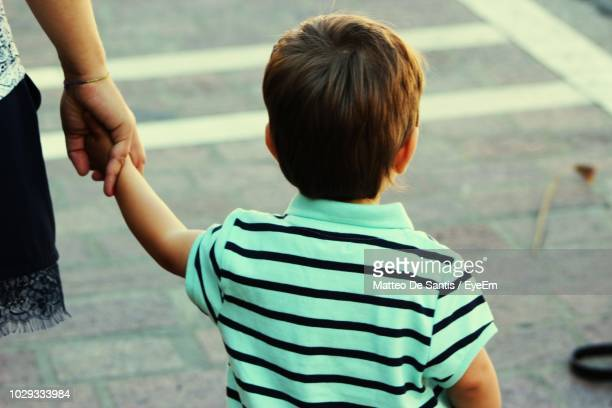 cropped image of mother holding son while walking on road - kin in de hand stock pictures, royalty-free photos & images