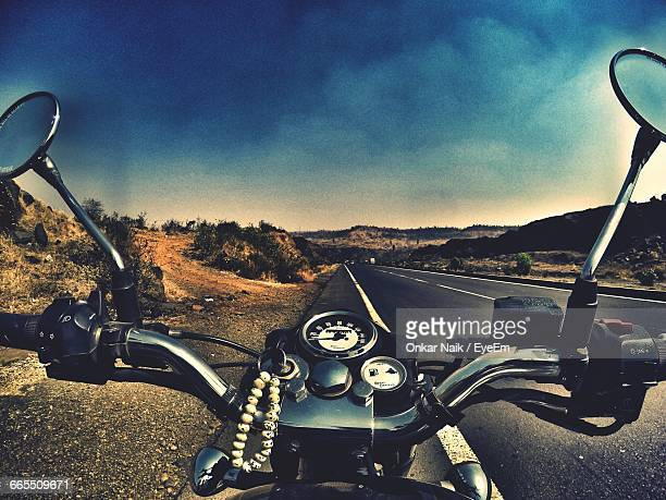 cropped image of motorcycle on country road against sky - handlebar stock photos and pictures