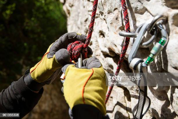 cropped image of mountain climber fixing rope and carabiners on rock - fastening stock pictures, royalty-free photos & images