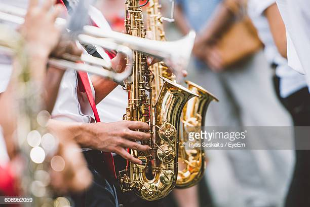 Cropped Image Of Musician Playing Trumpets And Saxophones