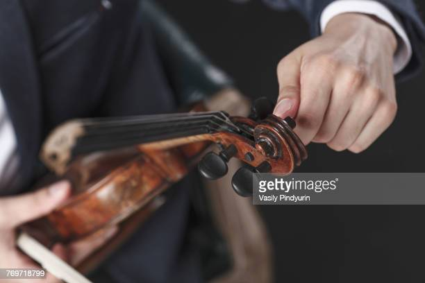 Cropped image of musician tuning violin strings