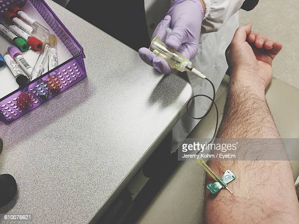 cropped image of nurse giving treatment to patient at hospital - iv drip womans hand stock pictures, royalty-free photos & images