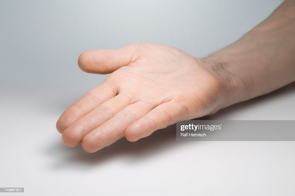 Cropped image of open hand over gray background : Stock Photo