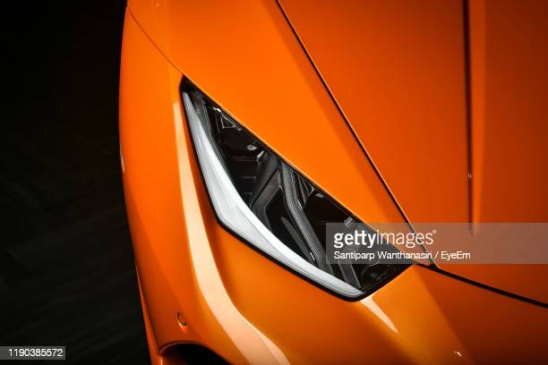 cropped image of orange car against black background - headlight stock pictures, royalty-free photos & images