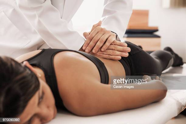 cropped image of osteopath treating female patient in clinic - osteopath stock photos and pictures
