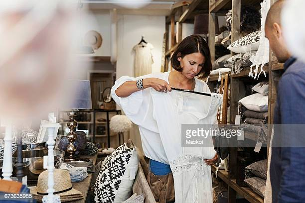 Cropped image of owner looking at female customer checking dress in store
