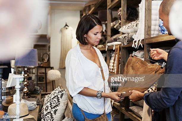 cropped image of owner showing brown skirt to female customer at store - older women in short skirts stock pictures, royalty-free photos & images
