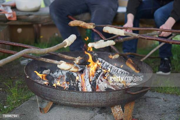 Cropped Image Of People Baking Breads On Sticks At Fire Pit