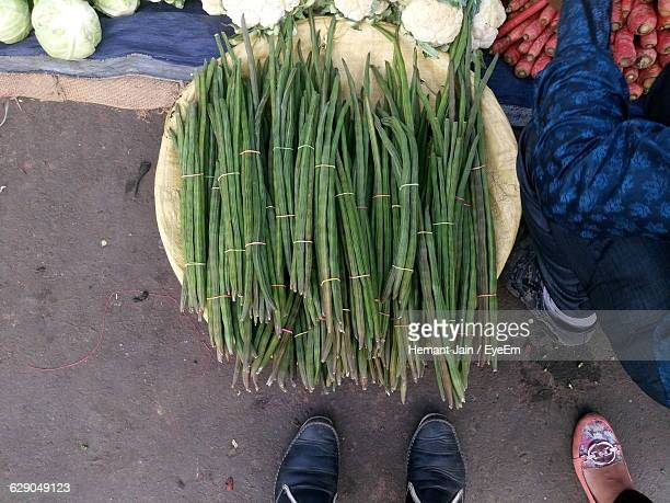 cropped image of people buying vegetables at market - moringa oleifera stock photos and pictures