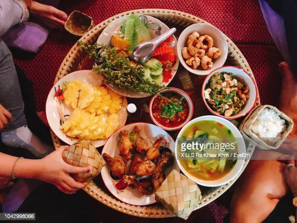 cropped image of people having food at table - thai food stock pictures, royalty-free photos & images