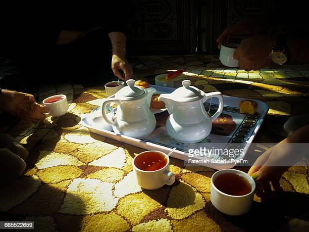 cropped image of people having tea together - persian culture stock photos and pictures