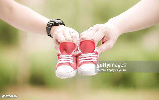 cropped image of people holding baby booties - baby booties stock photos and pictures