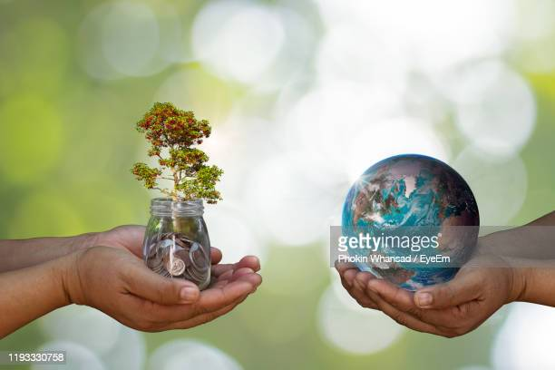 cropped image of people holding plant with coins in jar and globe - day 2 stock-fotos und bilder