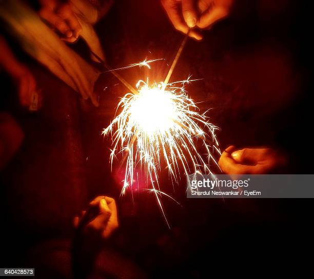 Cropped Image Of People Holding Sparklers During Diwali