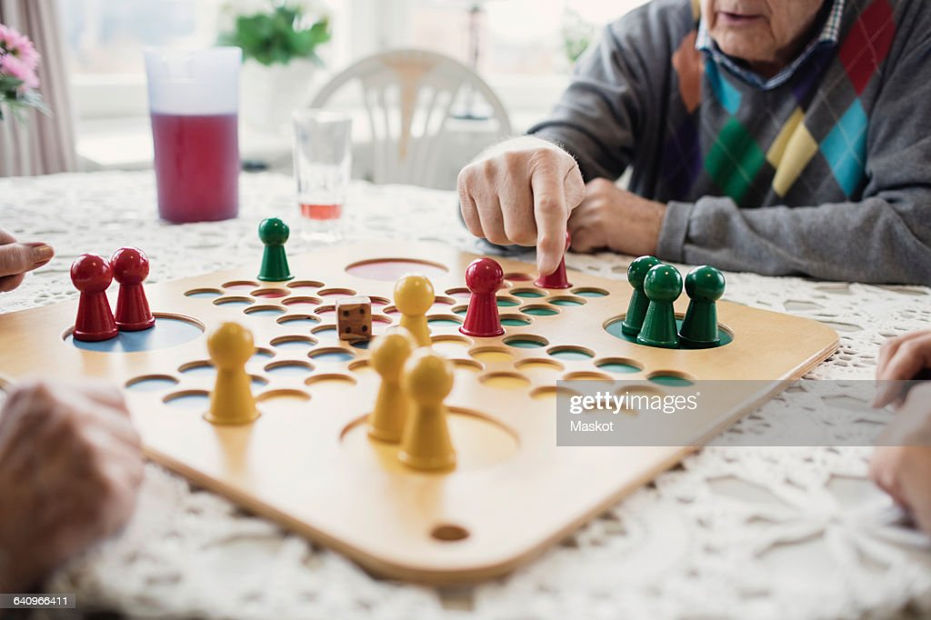 Cropped image of people playing Ludo in nursing home : Stock Photo