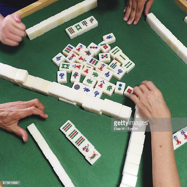 cropped image of people playing mahjong on table - mahjong stock photos and pictures