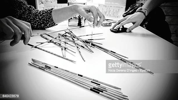 Cropped Image Of People Playing Pick Up Sticks On Table