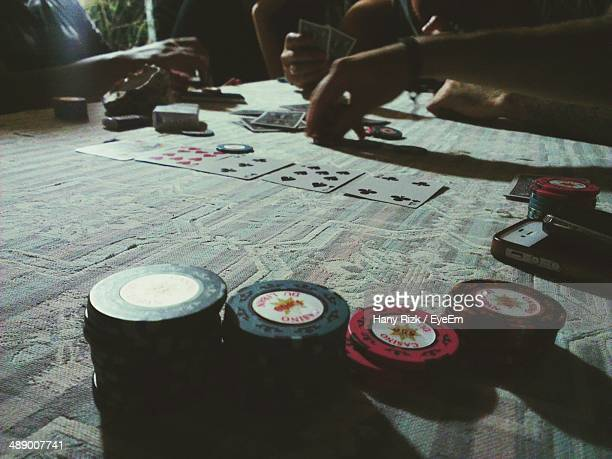 Cropped image of people playing poker at table