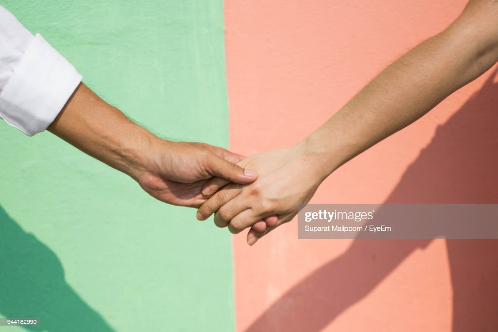 Cropped Image Of People With Holding Hands Against Wall : Stockfoto