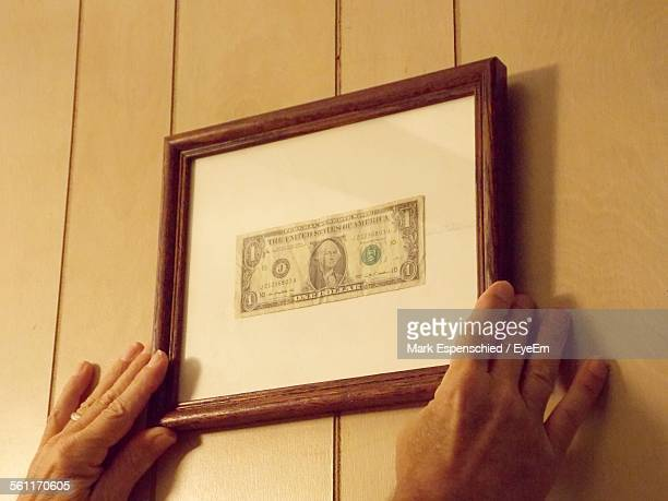 Cropped Image Of Person Adjusting Picture Frame With Dollar In It At Home