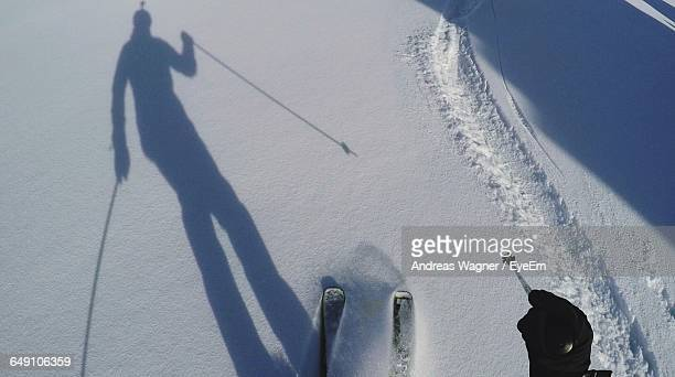 Cropped Image Of Person By Shadow Snowboarding On Snowcapped Mountain