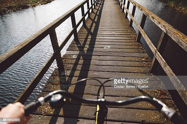 Cropped Image Of Person Cycling On Bridge Over River