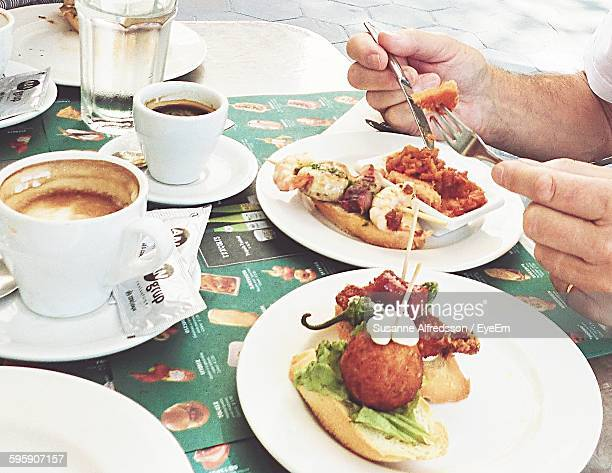 cropped image of person eating tapas with coffee at sidewalk cafe - tapas stock photos and pictures