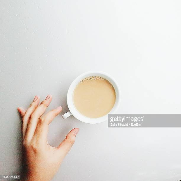 Cropped Image Of Person Hand By Coffee On Table