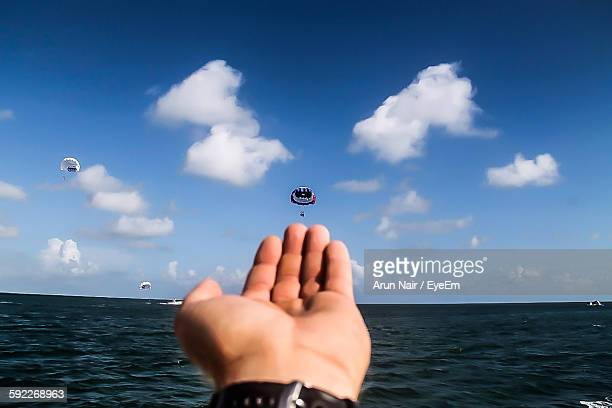Cropped Image Of Person Hand By Parachutes Flying Over Sea Against Sky