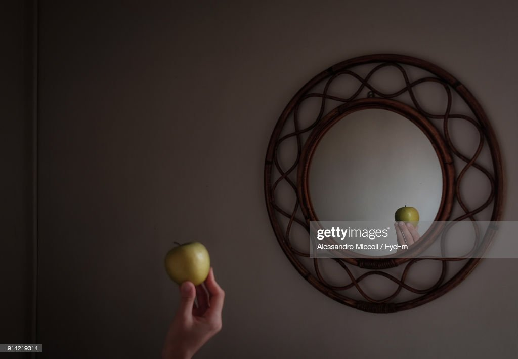 Cropped Image Of Person Holding Apple Against Mirror On Wall : ストックフォト