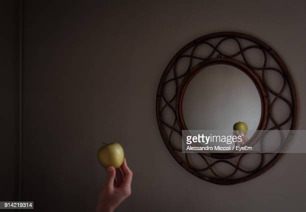 cropped image of person holding apple against mirror on wall - alessandro miccoli stockfoto's en -beelden