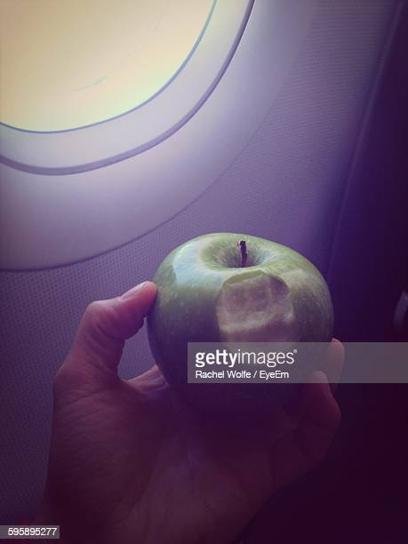 cropped image of person holding apple in airplane - rachel wolfe stock pictures, royalty-free photos & images