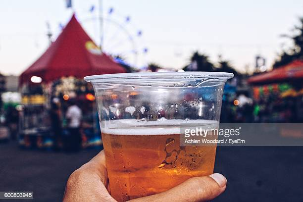 Cropped Image Of Person Holding Beer Glass At Carnival