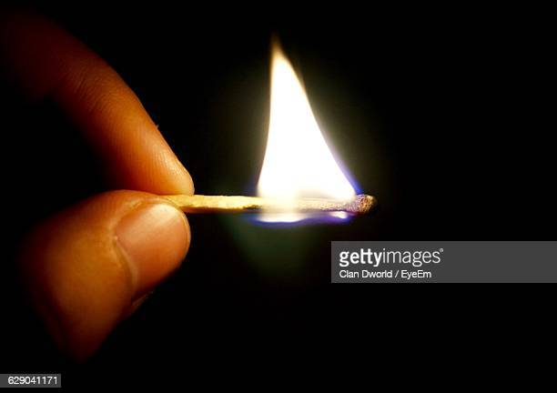 Cropped Image Of Person Holding Burning Matchstick Against Black Background