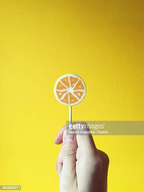 Cropped Image Of Person Holding Candy Against Yellow Background