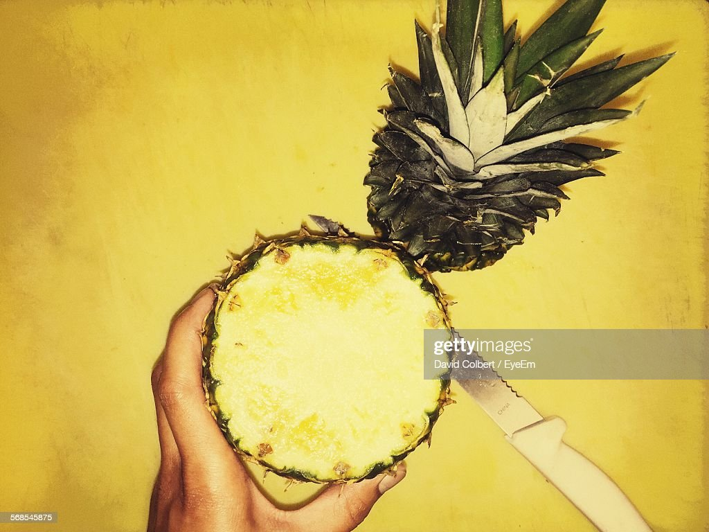Cropped Image Of Person Holding Chopped Pineapple Against Yellow Table : Stock Photo