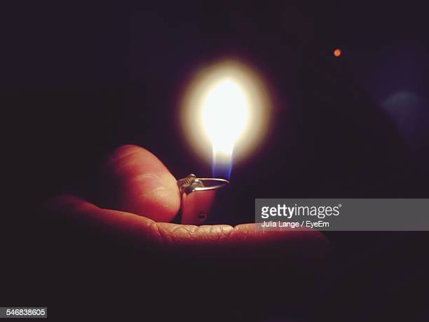 Cropped Image Of Person Holding Cigarette Lighter With Flame