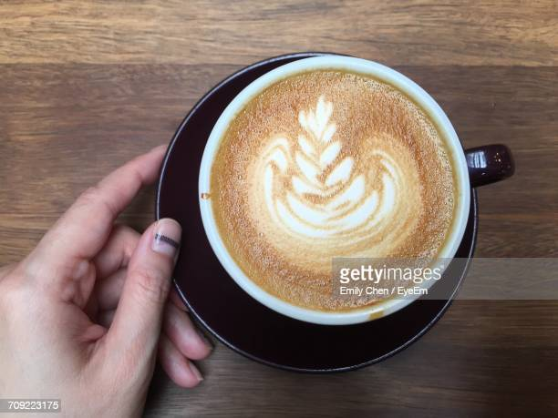 Cropped Image Of Person Holding Coffee At Table
