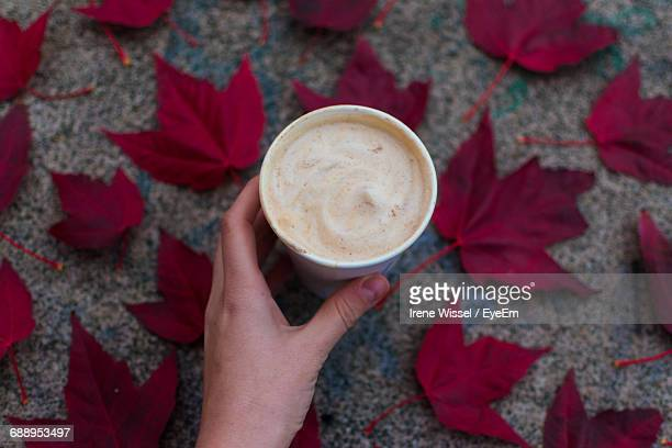 Cropped Image Of Person Holding Coffee Cup Amidst Autumn Leaves On Footpath