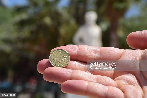 Cropped Image Of Person Holding Coin