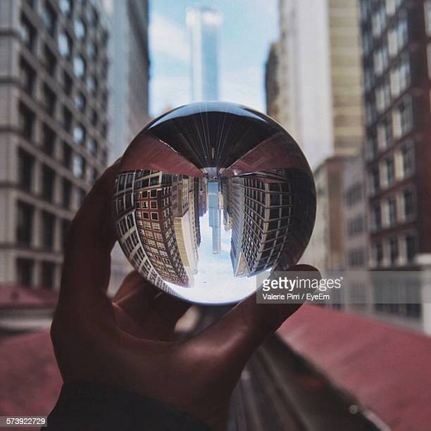 Cropped Image Of Person Holding Crystal Ball With Reflection Of Buildings